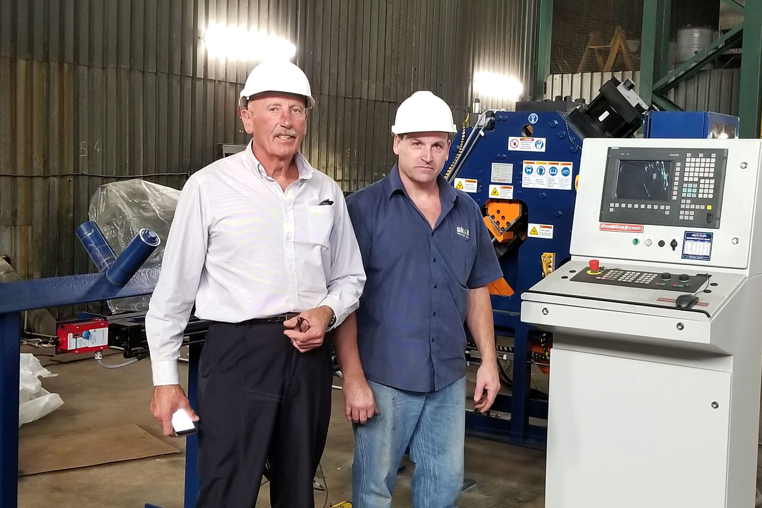 Ray Chellew and Sean Devenny of SKOK Machine tool in front of the Ocean Clipper CNC Angle Line at Pump and Steel Supplies Zimbabwe